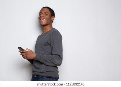 Profile portrait of happy african american man with cellphone against white background