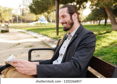 Profile portrait of happy businessman in suit smiling while sitting on bench in city park and reading newspaper