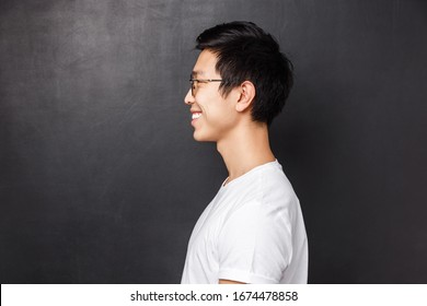 Profile portrait of happy smiling asian man in white t-shirt looking at left blank space, grinning friendly away as posing against black background, concept of people, emotions and advertising