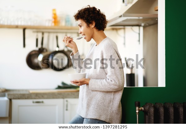 Profile portrait of happy young woman eating cereal at home kitchen