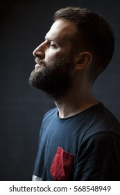 Profile portrait of a hip young bearded man isolated on black background