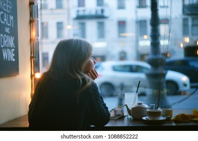 Profile portrait of a lonely blonde woman thinking in a coffee shop looking through the window at city street. evening