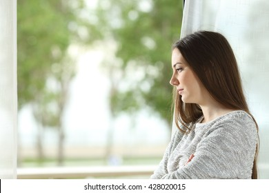 Profile portrait of a longing woman looking outdoors through a window at home or hotel room with a green background