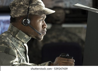 Profile portrait of a military drone operator at his computer