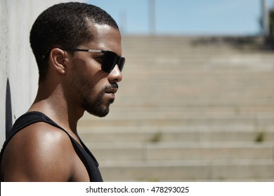 Profile portrait of muscular fit young African sprinter wearing black sleeveless shirt and sunglasses, leaning against concrete wall while waiting for his friends to join him in outdoor workout