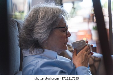Profile portrait of an older woman with glasses with a cup of tea in her hands and relaxed expression while is smelling the cup and sitting on a sofa