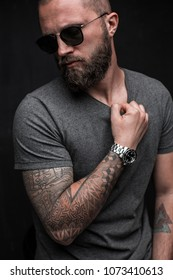 Profile portrait on turned head and long well trimmed beard of handsome man with sunglasses and grey shirt