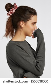 Profile portrait photo of a dark-haired girl, posing on a white background. She's wearing dark grey sweatshirt. Her hair is pulled back with pink velvet scrunchie.