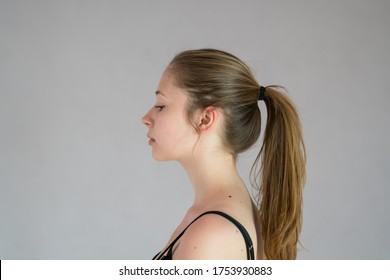 Profile portrait of a pretty teenage girl with ponytail hair. Studio shot