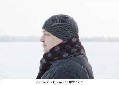 Profile portrait of senior man wearing knit cap, scarf and jacket standing in winter field during snowfall