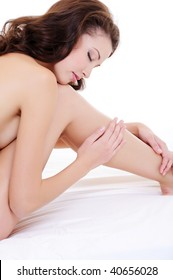 Profile portrait of a sexy  naked woman touching her beauty long legs sitting on the bed