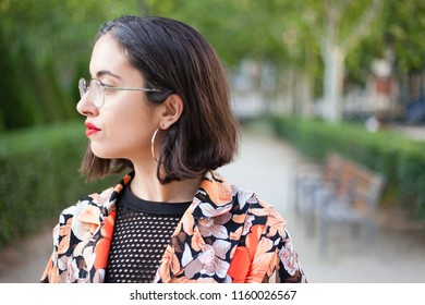 Profile portrait shot of trendy actual woman serious and confident on a Madrid outdoors park city background wih make up, big ear rings, flower shirt and fishnet. Spanish empowered woman.