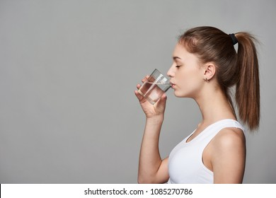 Profile portrait of sporty teen girl drinking clear water with closed eyes
