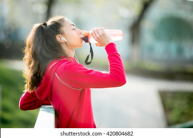 Profile portrait of sporty woman drinking in park after jogging. Female athlete runner getting ready for running routine. Fit girl listening music and enjoying drink with closed eyes outdoors