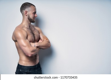 Profile portrait of a strong muscular man shirtless standing with folded hands by a wall looking forward at blank copy space