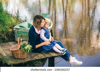 Profile portrait of white happy family of young mother and sweet little baby daughter sitting outside in countryside landscape background on spring day. Happy parenting. Horizontal color photography.