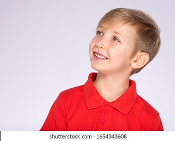 Profile portrait of white smiling kid in a red t-shirt looking away and up.  Photo of a thinking  boy looking away.  Caucasian boy with a sly look, thinking about. Pretty kid with a easy smile