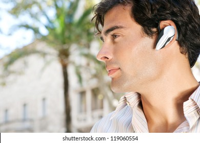 Profile portrait of a young attractive businessman using a hands free device to have a conversation on his cell phone while standing in front of classic office buildings in the city.