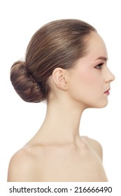 Profile portrait of young beautiful girl with hair bun over white background