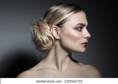 Profile portrait of young beautiful woman with fancy messy hair bun