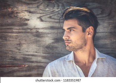 Profile portrait of young and handsome man on wooden background. He is wearing a white shirt and has a light beard.