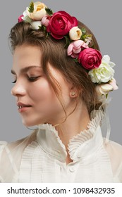 Profile portrait of a young lady with a wreath of magenta, white and peach pink peonies. The romantic girl looking down thoghtfully against the grey background, a gorgeous flower crown on her head.