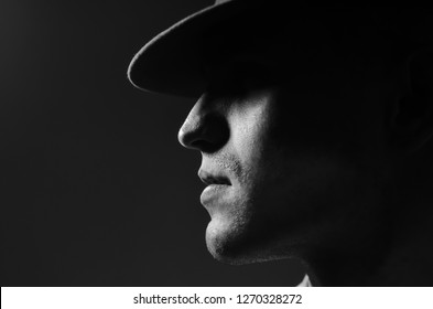 Profile portrait of a young man in a hat standing over dark gray background. Close up. Classic style. Copy-space.  in bright light in fashionable style