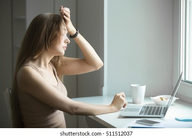 Profile portrait of a young serious woman, touching her forehead, overworked after working at laptop, small home office interior. Business concept photo, lifestyle