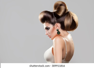 Profile portrait of young sexy woman with creative hairstyle and nice makeup in studio