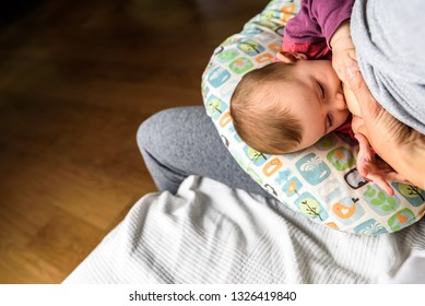 Profile portrait of a young woman breastfeeding a child using a special breastfeeding pillow for newborn babies.