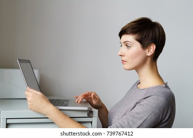 Profile portrait of young woman standing by file cabinet with laptop at office