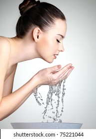 Profile portrait of young woman washing her face with clean water - studio