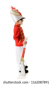 Profile of a preschool Christmas soldier standing eret with his gun by his side.  On a white background.