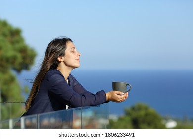 Profile of a relaxed woman in a hotel balcony with a cofee cup on the beach on summer vacation