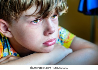 Profile of a sad crying boy with a tear on his cheek. The child is grieving. The child is mourning the loss. Bullying at school. The crisis of schoolchildren. Sorrow for the victims of coronavirus