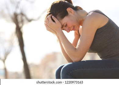 Profile of a sad teen crying desperately sitting on a bench in a park