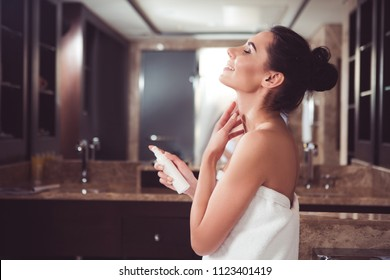 Profile of satisfied woman applying cream on neck with joy. She is holding cosmetic container in one hand while gently touching skin with another. Copy space in left side