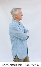 Profile of senior man standing with crossed arms
