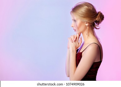 profile of sensual blonde model woman in colorful bright lights in studio. pink and blue color