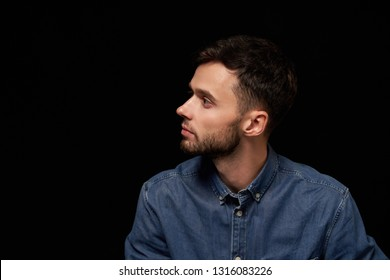 Profile of serious handsome man in denim shirt looking aside at blank copy space, over black background