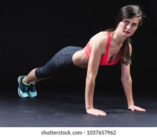 Profile of a serious woman doing plank exercises at studio