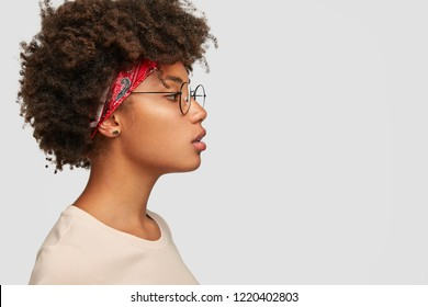 Profile of serious woman with healthy pure skin, has bushy hairstyle, wears round glasses, has contemplative expression, ready to have outdoor walk, isolated over white studio wall with copy space