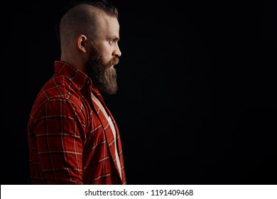 profile of serious young bearded man standing against black background