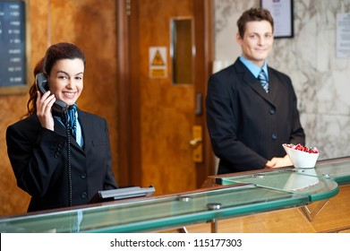Profile shot of attractive executives at the reception of a hotel. Woman attending phone call