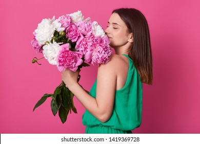 Profile shot of beautiful brunette girl holding with white and rose peonies, attractive woman with big bouquet, female smells flowers, dressed green sundress, posing against yellow pink background.