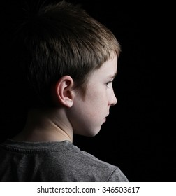 A profile shot of a boy on low key black from behind