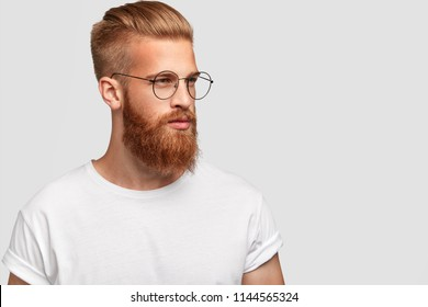 Profile shot of brutal male with thick foxy beard, wears round glasses and looks thoughtfully aside, dressed casually, isolated over white background with blank space aside for your text or promotion