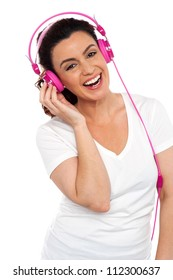 Profile shot of a cheerful young beautiful lady enjoying music on her pink headphones