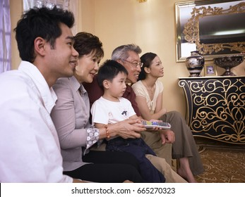 profile shot of a family watching television together