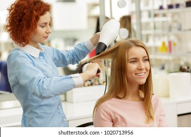 Profile shot of a ginger haired professional female hairdresser using hairdryer while styling her female client beautiful young woman getting a new haircut at the beauty salon profession service